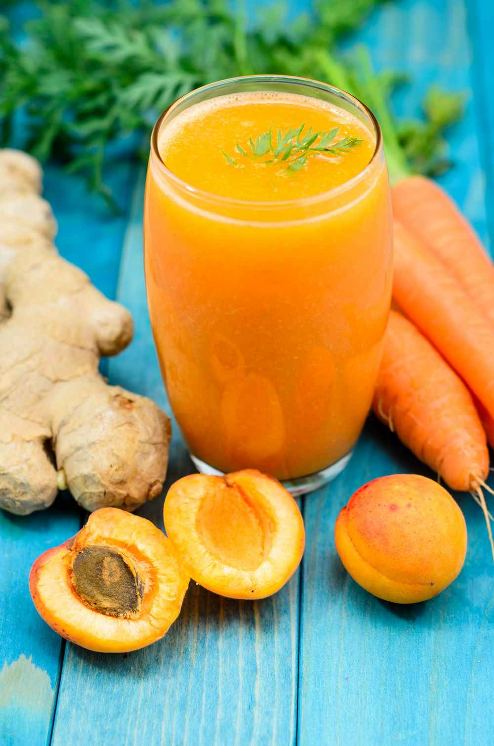 juice fasting recipe - thenaturalhealthdictionary.com - glass-of-apricot-carrot-juice-on-blue-wooden-table-1150682